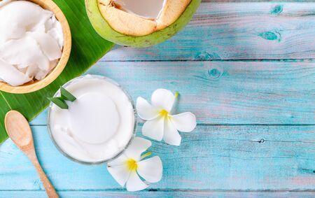 Junger Kokospudding, der in einer mit Kokosfleisch verzierten Glasschale serviert wird, sieht auf den Bananenblättern und einem schönen blauen Holztisch köstlich aus. Ansicht von oben.