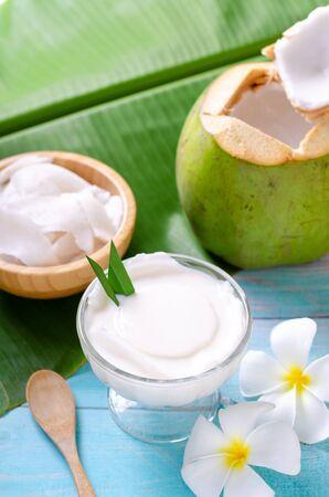 Junger Kokospudding, der in einer mit Kokosfleisch verzierten Glasschale serviert wird, sieht auf den Bananenblättern und einem schönen blauen Holztisch köstlich aus.
