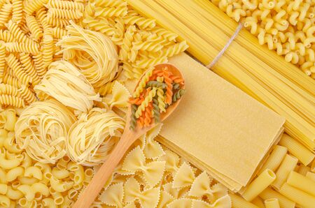 Variety of types and shapes of dry raw Italian pasta , wooden spoon on pasta and dry lasagna sheet that can put text.