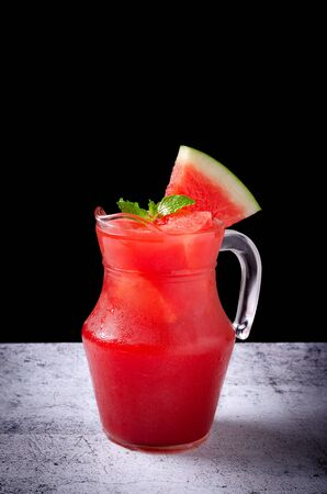Watermelon juice in jar with slices of watermelon.