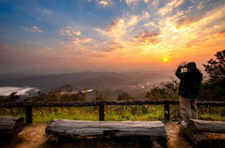 Tourists standing on the edge of the cliffs taking pictures of the sunrise at Doi Samer Dao. See the mountains, the sea of mist and the sunrise in the morning.