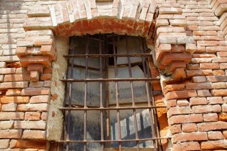 ferro: antica finestra in mattoni rossi con grata ferro battuto Stock Photo