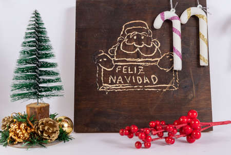 Wooden board with a drawing of Santa Claus holding a Merry Christmas sign in Spanish. Christmas tree with white canes with colored strips and colored balls on white background.