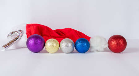 Santa Claus hat on a white background with balls of various colors and a silver cane.