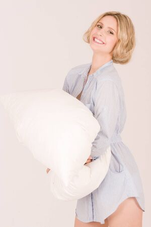 smiling young woman with a pillow in the morning photo