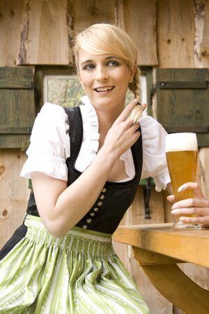 Young woman in dress sitting in the beer garden and drink  photo