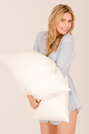 smiling blonde beauty in pajamas shirt with pillows in hand