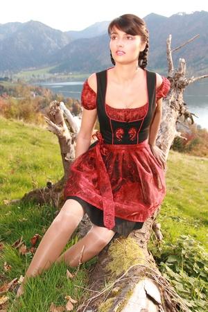Bavarian Dirndl girls sitting on a tree trunk Stock Photo