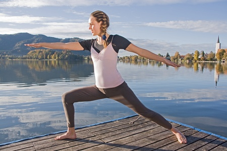 omitted: Young woman meditating in yoga by the lake
