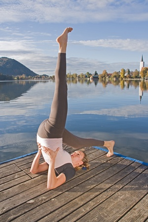 Young woman meditating in yoga by the lake photo