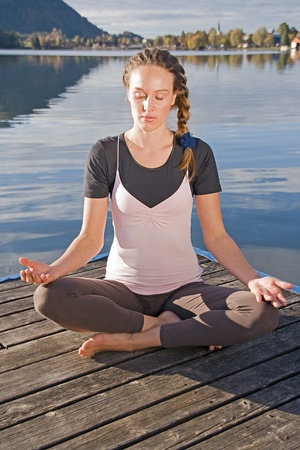 Young woman meditating in yoga by the lake