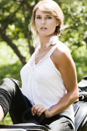 Fashionable young woman on an old motorcycle
