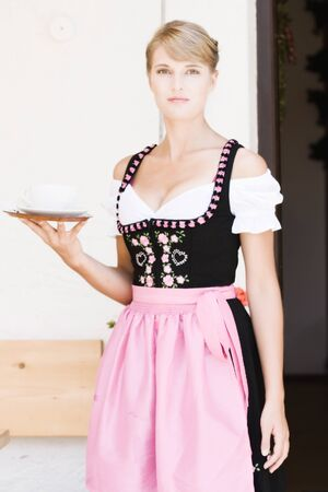 Bavarian Dirndl woman serving coffee on the pasture