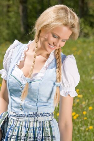 Bavarian Dirndl laughing blonde girl on the meadow Stock Photo