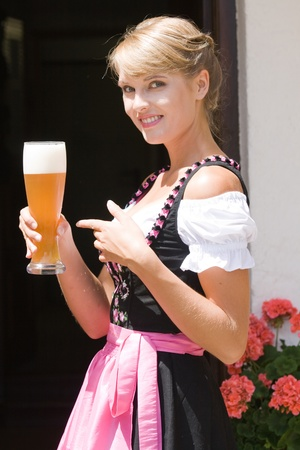 Young Bavarian operation served a glass of white beer photo