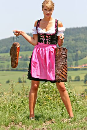 Young Bavarian girl with fresh bacon on the meadow