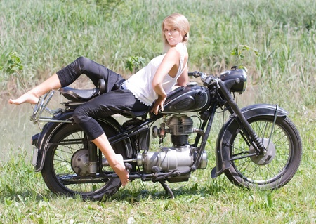 fashionably: Fashionably dressed woman seated on an old motorcycle