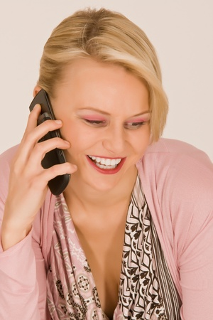 Fashionable young woman at the phone with a mobile phone photo