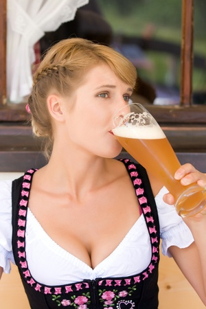 Bavarian white beer-drinking woman in traditional dress