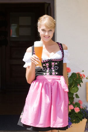Young woman in dirndl wheat beer served in a mountain economy Stock Photo - 10401748