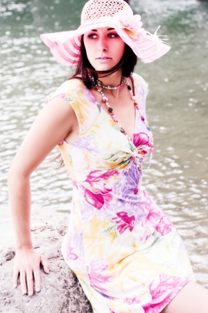 Young Plus Size Model in a summer dress and hat at the lake Standard-Bild