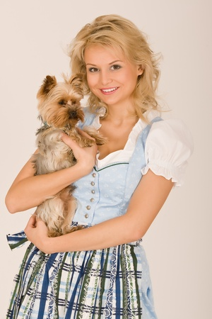 Young Bavarian girl with a dog on his arm photo