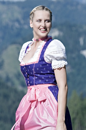 hostile: Beautiful girl on a Bavarian alpine meadow in the mountains