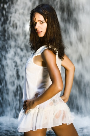 Young beauty posing under a waterfall
