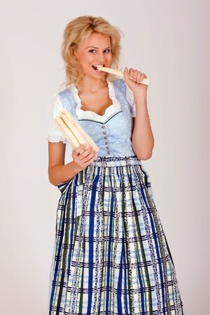 Beauty in Bavarian costume with asparagus in her hand photo