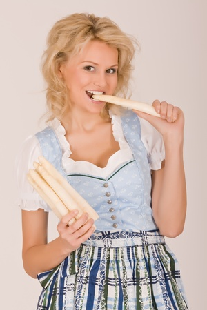 Beauty in Bavarian costume with asparagus in her hand Stock Photo