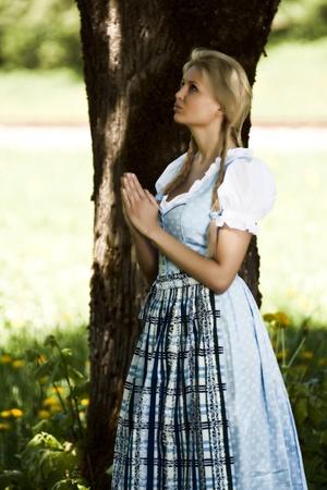 dirndl: Bavarian girl under a tree when praying