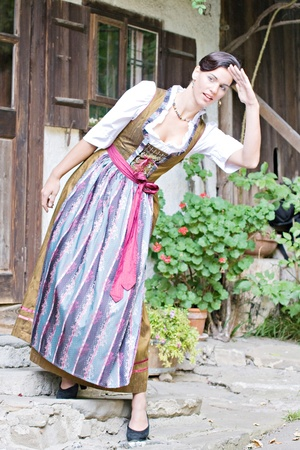 Bavarian girl in Holiday costume sitting on a bench