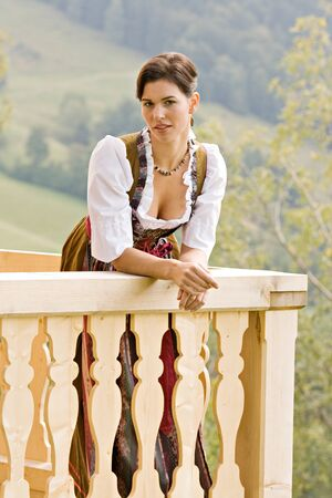 in vouge: Bavarian girl in Holiday costume sitting on a bench