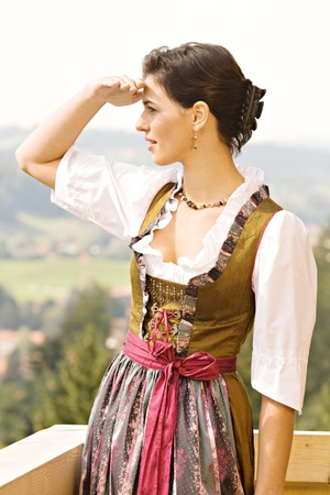 bosom: Bavarian girl in Holiday costume sitting on a bench