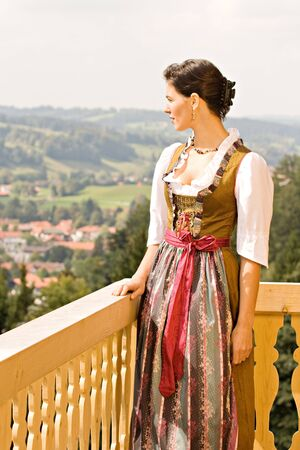 vouge: Bavarian girl in Holiday costume sitting on a bench