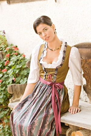 Bavarian girl in Holiday costume sitting on a bench Stock Photo - 10487143