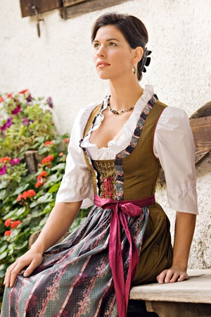 dirndl: Bavarian girl in Holiday costume sitting on a bench