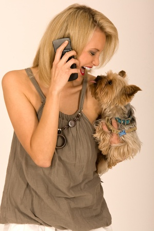Woman with dog on the phone at arm photo