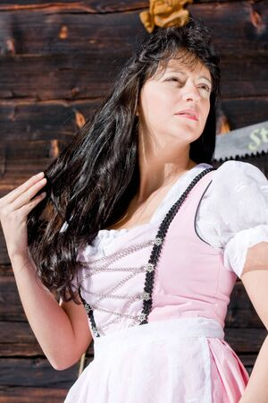 Bavarian girl in fashionable dress in front of a hut photo