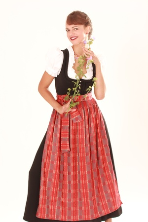 Bavarian woman in traditional dress posing with fragrant flower