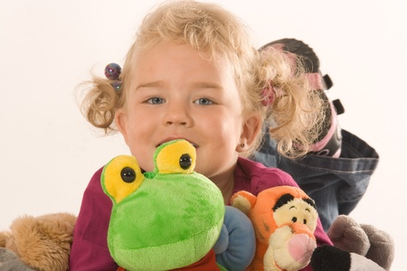 Little blonde girl with your favorite stuffed animals photo