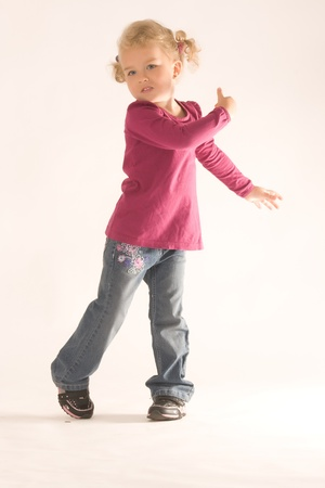 Little blonde girl with curly hair has fun at the dance Stock Photo - 10826093