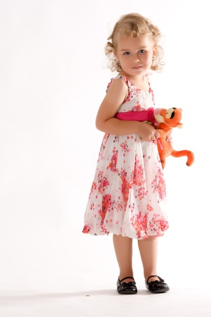 Little blonde girl in fashionable dress and soft toy in the hand Stock Photo - 10826091