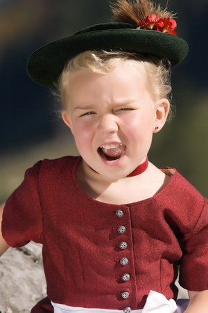 Little blonde girl in typical Bavarian costume and singing on the mountain Standard-Bild
