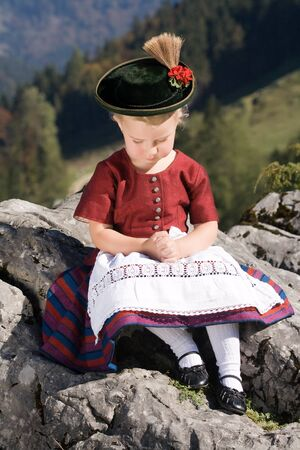 uniform curls: Little blonde girl in typical Bavarian costume on the mountain and pray Stock Photo