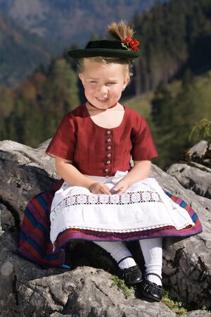 uniform curls: Little blonde girl in typical Bavarian costume on the mountain