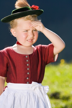 Little blonde girl in typical Bavarian costume on the mountain and looks into the country Standard-Bild