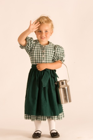 Little girl with blond curly hair Bavarian in traditional dress with milk jug
