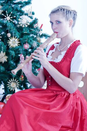 Young woman in traditional Bavarian dress during non flutes playing in front of a Christmas tree Stock Photo - 11148244
