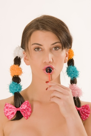 Girl with colorful braids licking a lollipop photo